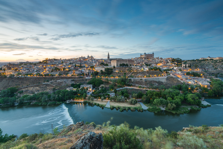 Ponoramic cityscape of Toledo in Spain with illuminated streets and river Tangus in valley.