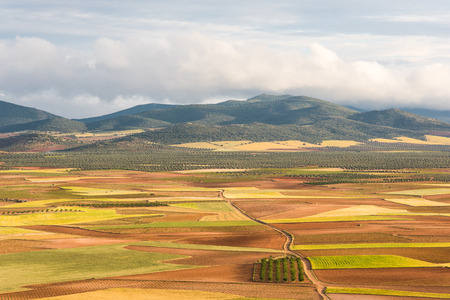 Rural farming landscape in Castila La Mancha,Spain with mountains in clouds on horizon