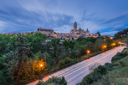 Segovia cathedral at evening illuminated, Spain with light trails from passing cars and rooling dramatic clouds. Editorial