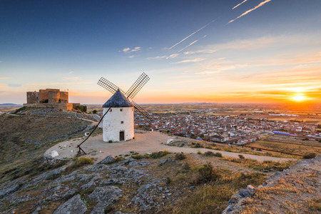 don quijote: Sun rising over COnsuegra with legendary windmills and castle on hill top