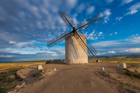Ancient windmill on hill top with rural landscape and summer blue sky