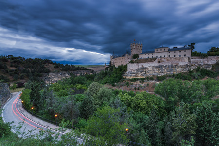 Historic Alcazar in Segovia with dramatic storm clouds rolling, illuminated at twilight, Spain