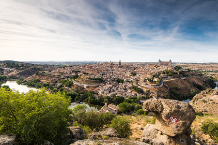 Panoramic daylight view over Toledo from elevated viewpoint down into valley of river Tagus.