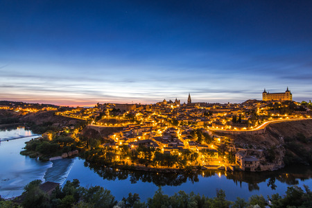 Night cityscape of illuminated Toledo in Spain and tranquil river Tagus in valley.