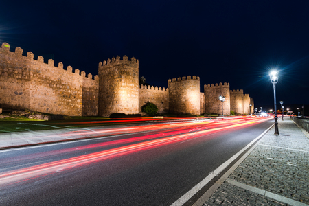 Light trials of cars and Avila walls in background Editorial