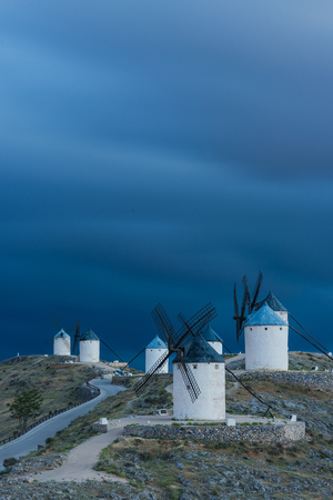 mancha: Evening clouds and medieval windmills on hill top, Consuegra,Spain