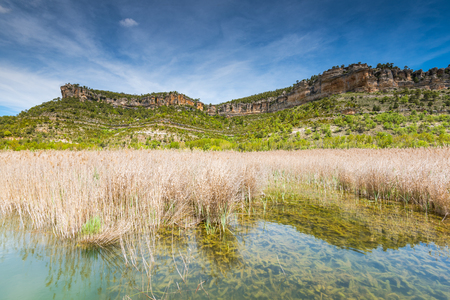 Mountains reflection in lake with grass, Una lagoon near Cuenca,Spain Stock Photo