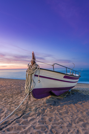 Fishing boat on sandy beach at nostalgic sunrise in Barcelona,Spain
