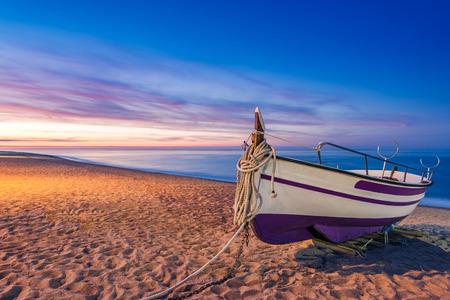Oude houten vissersboot op het strand bij zonsopgang, Pineda de Mar, Barcelona, Spanje Stockfoto