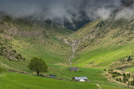 Farmlands in high Pyrenees,Andorra with low clouds in mountains.
