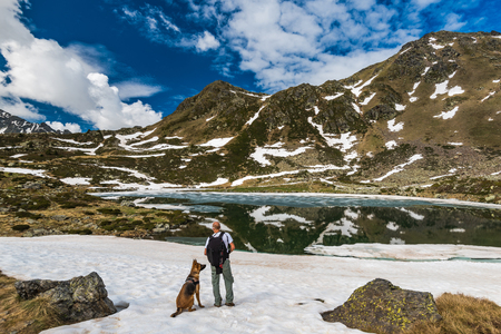 Active hiker on trial with dog in Pyrenees standing on snow, Andorra Stock fotó - 91192817