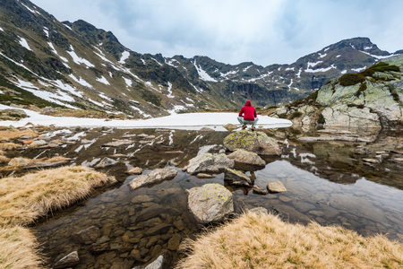 Hiker sits on rock near lake Tristaina in Andorra Pyrenees