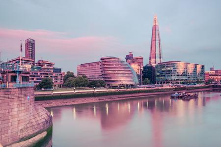 De wolkenkrabbers van Londen wijzen in de rivier van Theems op kleurrijke zonsopgang