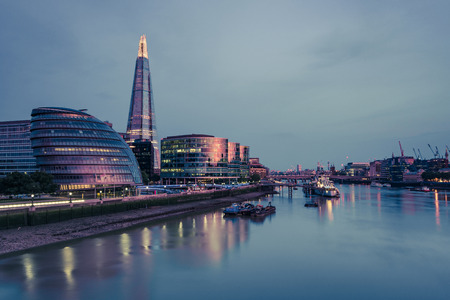 View from Tower Bridge in London at illuminated cityscape.