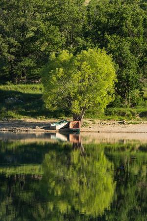 静かな湖でノスタルジックな木造船の反射。