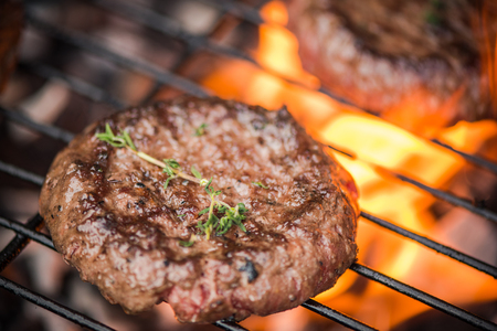 close up burger on bbq over flames