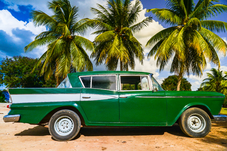 Old american car under Cuban palm on the beach. Stock Photo