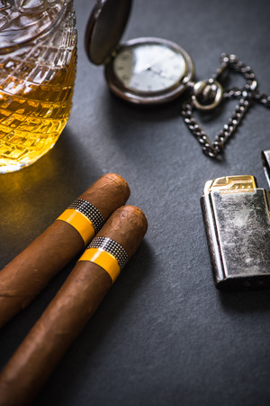 Cuban cigar with lighter and old watch.