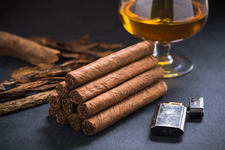 Many cuban cigars in stack with cognac.