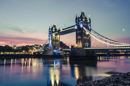 London Tower Bridge illuminated at dusk with water reflection Фото со стока
