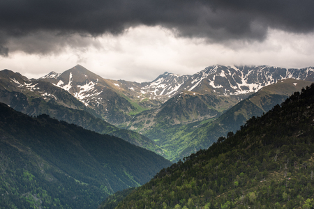 Moody and dramatic clouds over Pyrenees mountains peaks