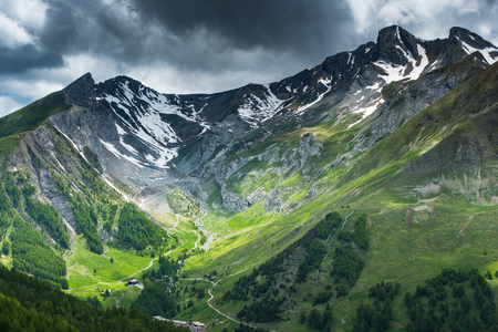 Stunning valley at foot of the French Alps with snowy peaks and thunderstorm clouds. Stockfoto