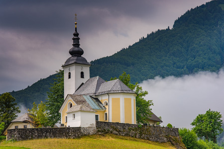 Church of saint Nikolaja in Sorica, Slovenia with low clouds in mountains