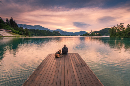 Man and dog sitting on wooden deck at Bled lake, Slovenia watching sunrise