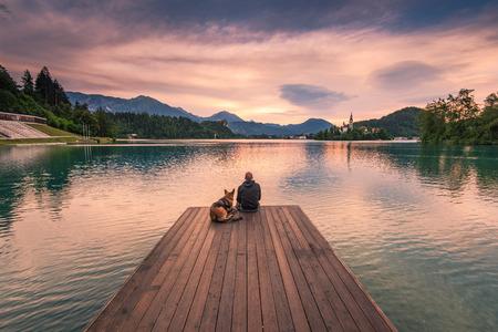 Mens en hondzitting op houten dek bij het meer van Bled, Slovenië die op zonsopgang letten