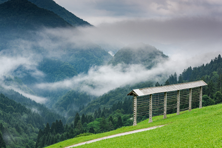 Traditional farming, hayrack in Slovenia mountains at misty day.