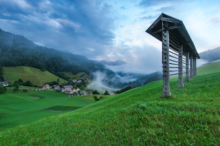 Hayrack on hilltop and Sorica village in Slovenia.