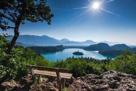 Bled 호수를 내려다 보이는 벤치 전체 여름 태양에서 파노라마 비스타. 스톡 콘텐츠