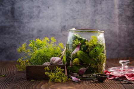 木製テーブルの上の冬の漬物のきゅうりを瓶を充填します。