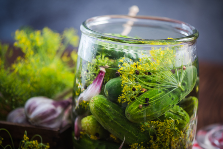 Glass jar filled with gherkins and cucumber for winter. Pickles recipe with ingredients. Banco de Imagens