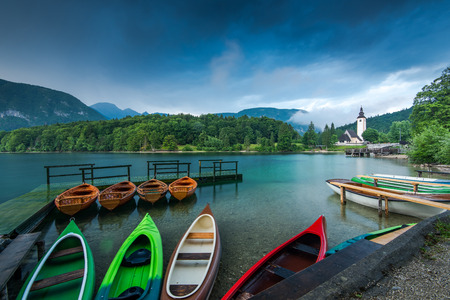 Colorful kayaks at lake Bohijn, Slovenia. Stok Fotoğraf - 81971290