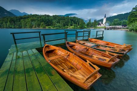 Wooden leisure boats at wooden pier at lake Bohijn, Slovenia.
