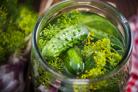 Traditional organic savory pickled gherkins and cucumbers in glass jar Banco de Imagens - 82083169