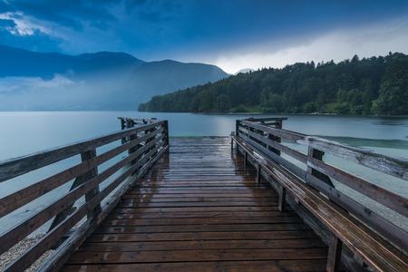 Wooden pier at lake Bohijn, SLovenia at rainy evening.