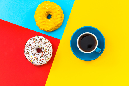 Coffee cup and donut minimalistic colorful design, flat lay and top view