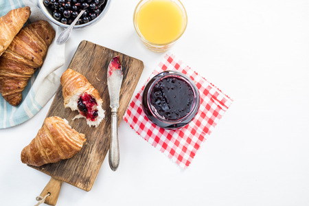 Fresh croissant with blueberry marmelade served on wooden board
