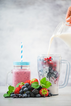 Pouring milk into blender, smoothie making.