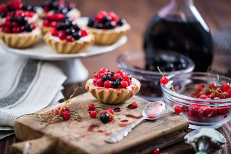 Het maken van zwarte en rode aalbestaart met kwark. Ingrediënten op houten tafel. Stockfoto