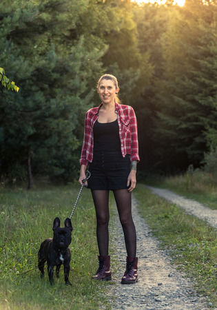 Hipster girl with tattoo walking French Bulldog in forest. Sun flare effect.
