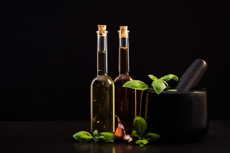 Gegoten olijfolie, stamper en specerijen op donkere stenen leisteen