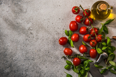 Cherry tomatoes with fresh basil and olive oil. Clean eating and healthy diet concept. Border background on concrete slate.