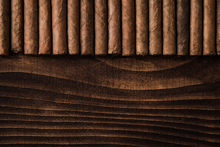Cuban cigars close up on wooden table, border background. Directly from above top view Imagens