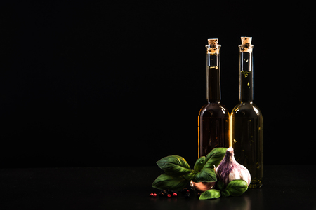 Olive oils in bottles with herbs and spices. Banco de Imagens