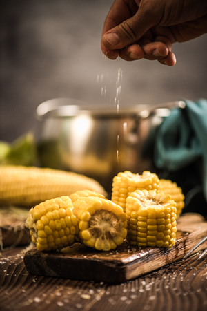 Hand salting hot cooked corn on the cob. Serving cooked autumn snack. Stock Photo