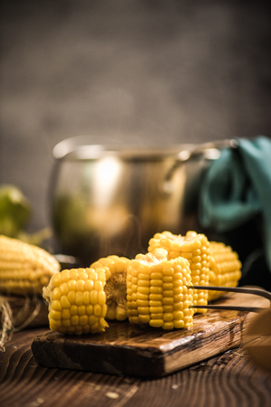 Steaming hot cooked corn on wooden rustic board Stock Photo