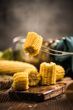 Hot cooked corn on the cob being served on wooden rustic board Stock fotó